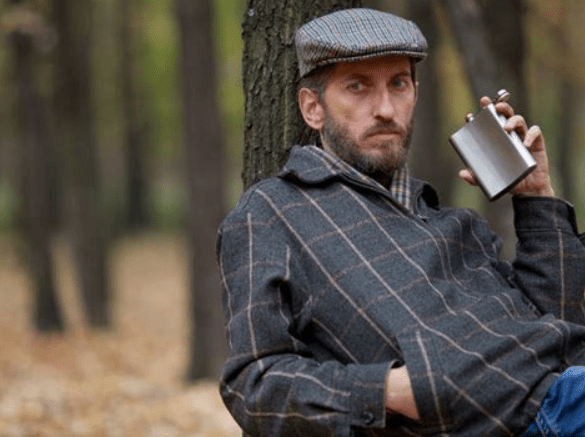 Man drinking from hip flask