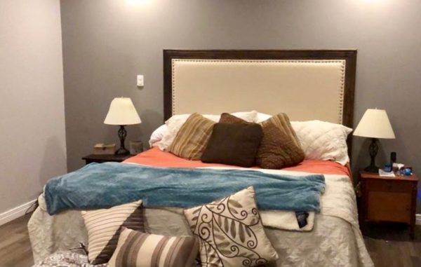 King size bed with upholstered headboard in linen and brass tacks