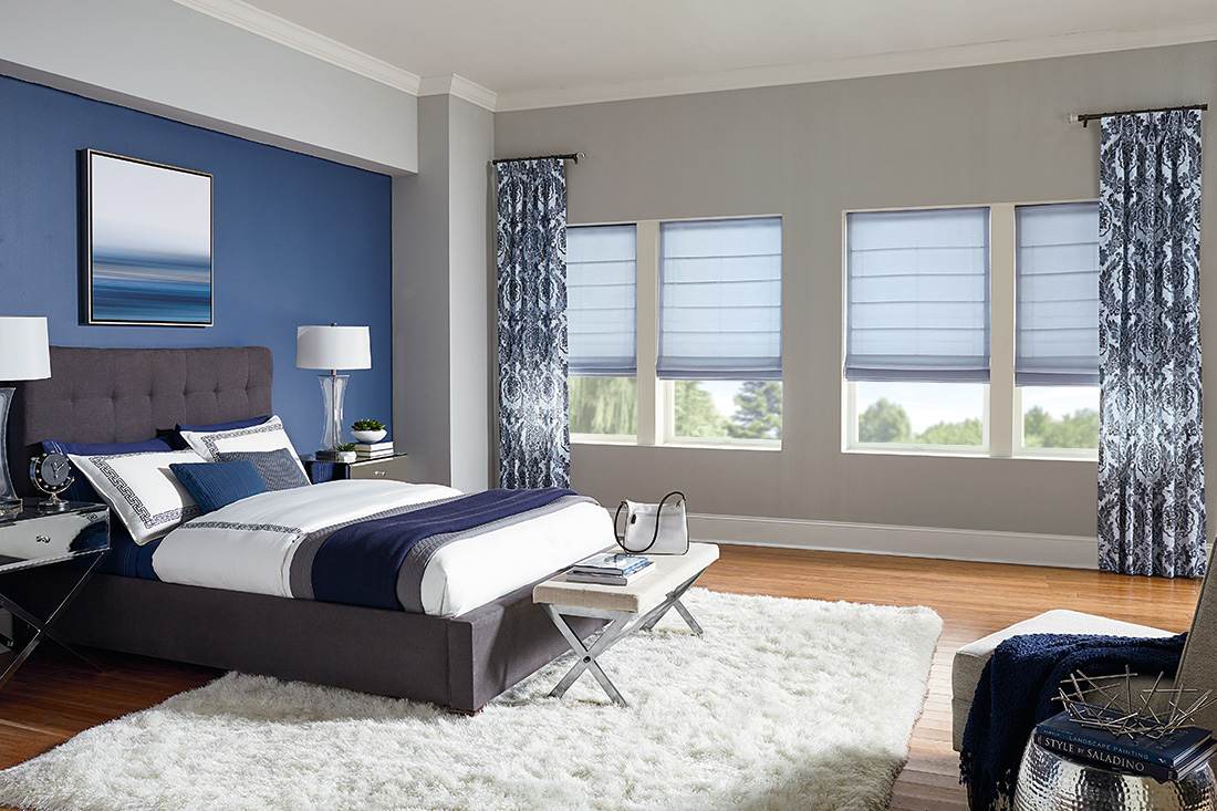 Hobbled roman shades offer soft texture while bold side panels draw attention to natural light with Comfortex Window Fashions.