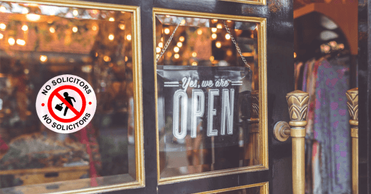 """Store Front with a Glass Pane Door, a """"We're Open Sign"""" Hangs on the Inside"""