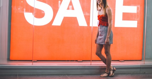 Woman Standing in Front of an Orange SALE Sign