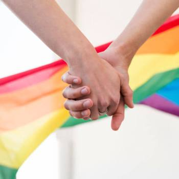 holding hands in front of rainbow flag