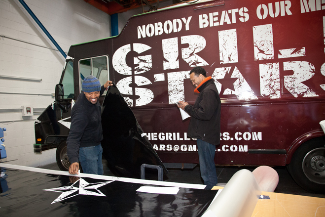 Kwasi Boyd (left) and Sandor Price check details on the finished Grill Stars Truck at Custom Vehicle Wraps. Photo by Lori Eanes for the Wall Street Journal.