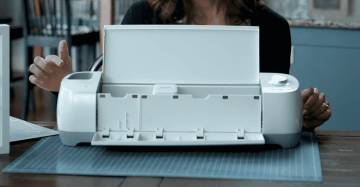 A woman points to the cartridge slot on a Cricut Explore.