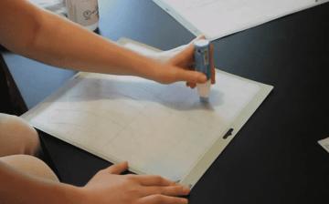 A woman applies Zig 2-way Glue to her Cricut mat to make it sticky again