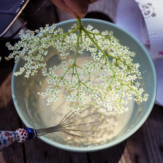 Für die Holunderblütenpancakes tauche ich Holunderblüten in Pancake Teig