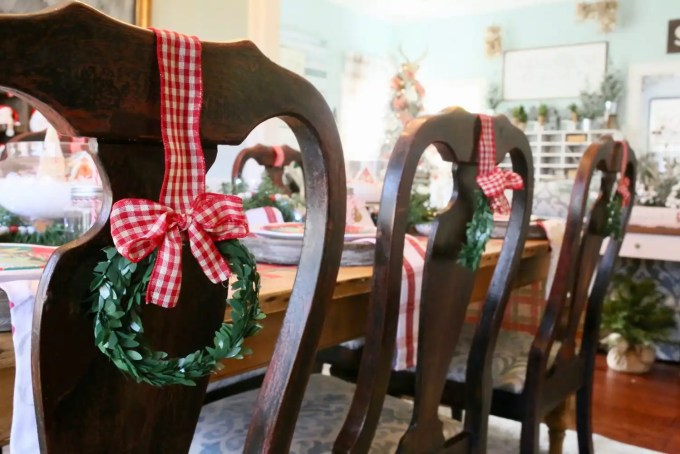 mini wreaths tied to the back of dining chairs