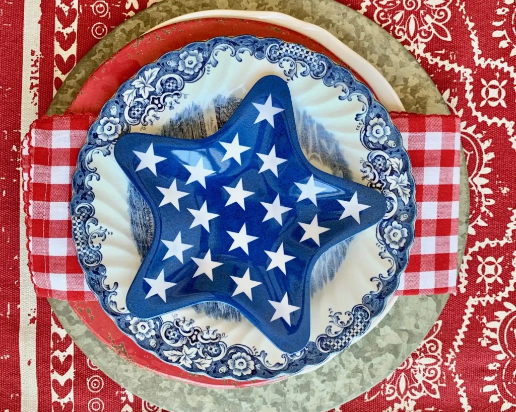 Star shaped plate layered over blue and white transfer ware, red and white checkered napkin and galvanized charger.