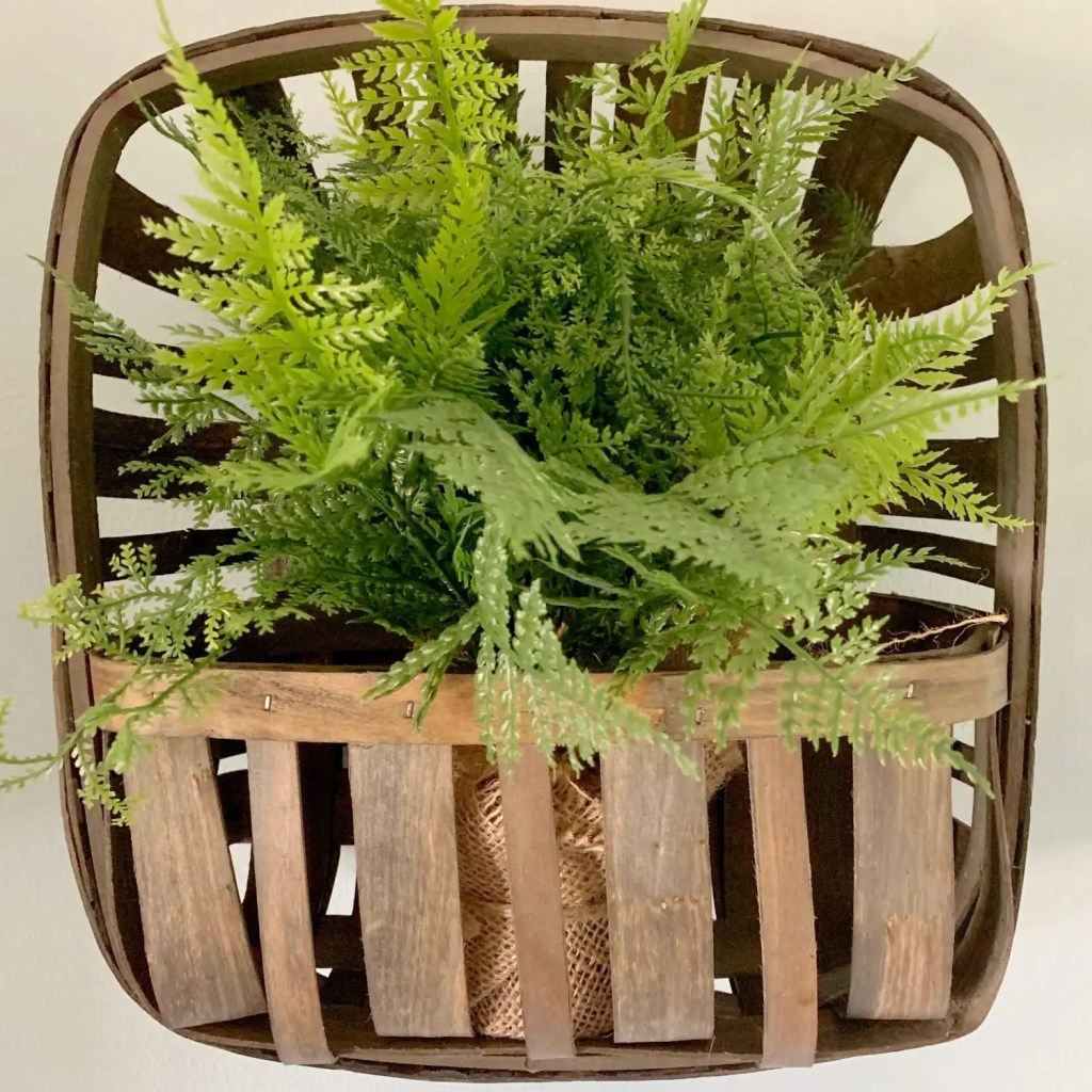 Burlap wrapped greenery in tobacco wall basket.