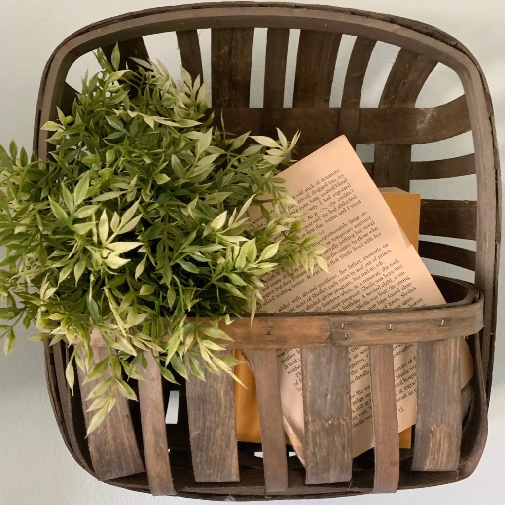 Deconstructed books and greenery orb in tobacco wall basket provide a farmhouse feel.