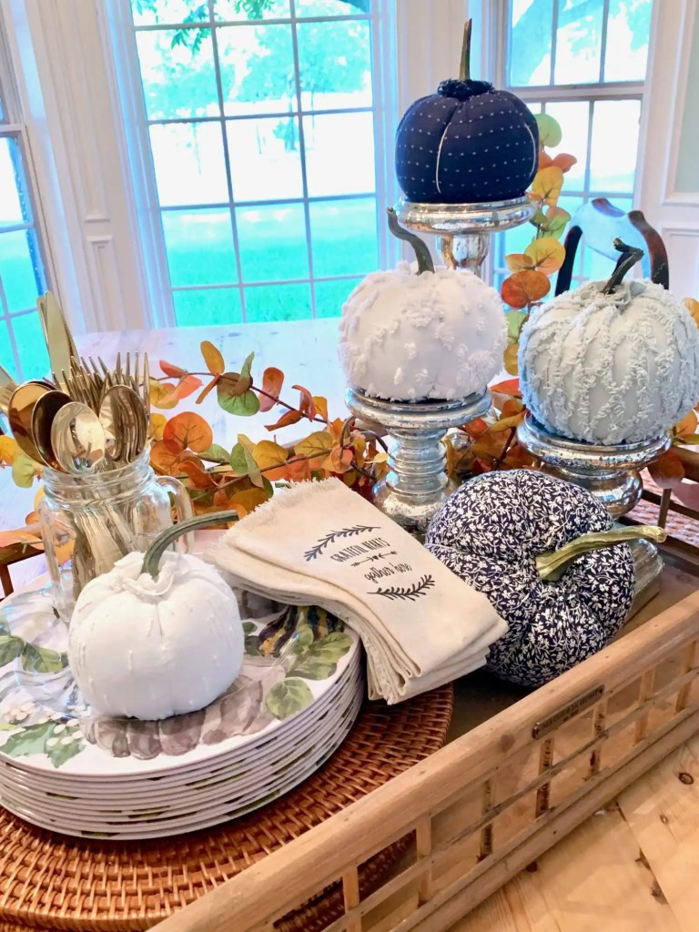 A large tray with candlesticks, pumpkins and dishes acts as a dining room table centerpiece for Fall.