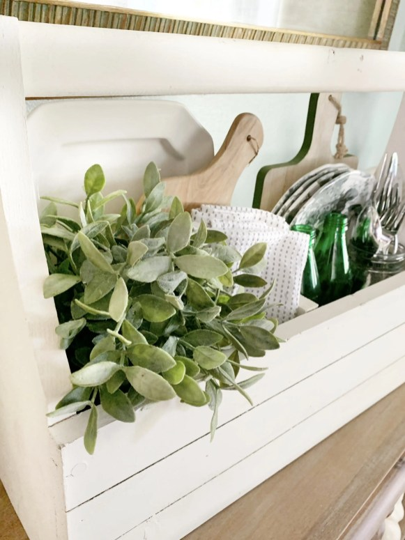 Cutting board displayed in vintage crate with plant, linens, white dishes.