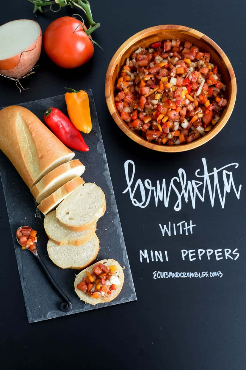 Bruschetta with Mini Peppers served on slate platter with title written on chalkboard overhead shot