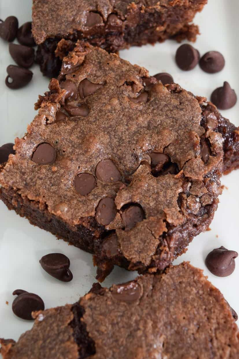 Chocolate Chip Brownies sliced on white platter sprinkled with chocolate chips overhead shot