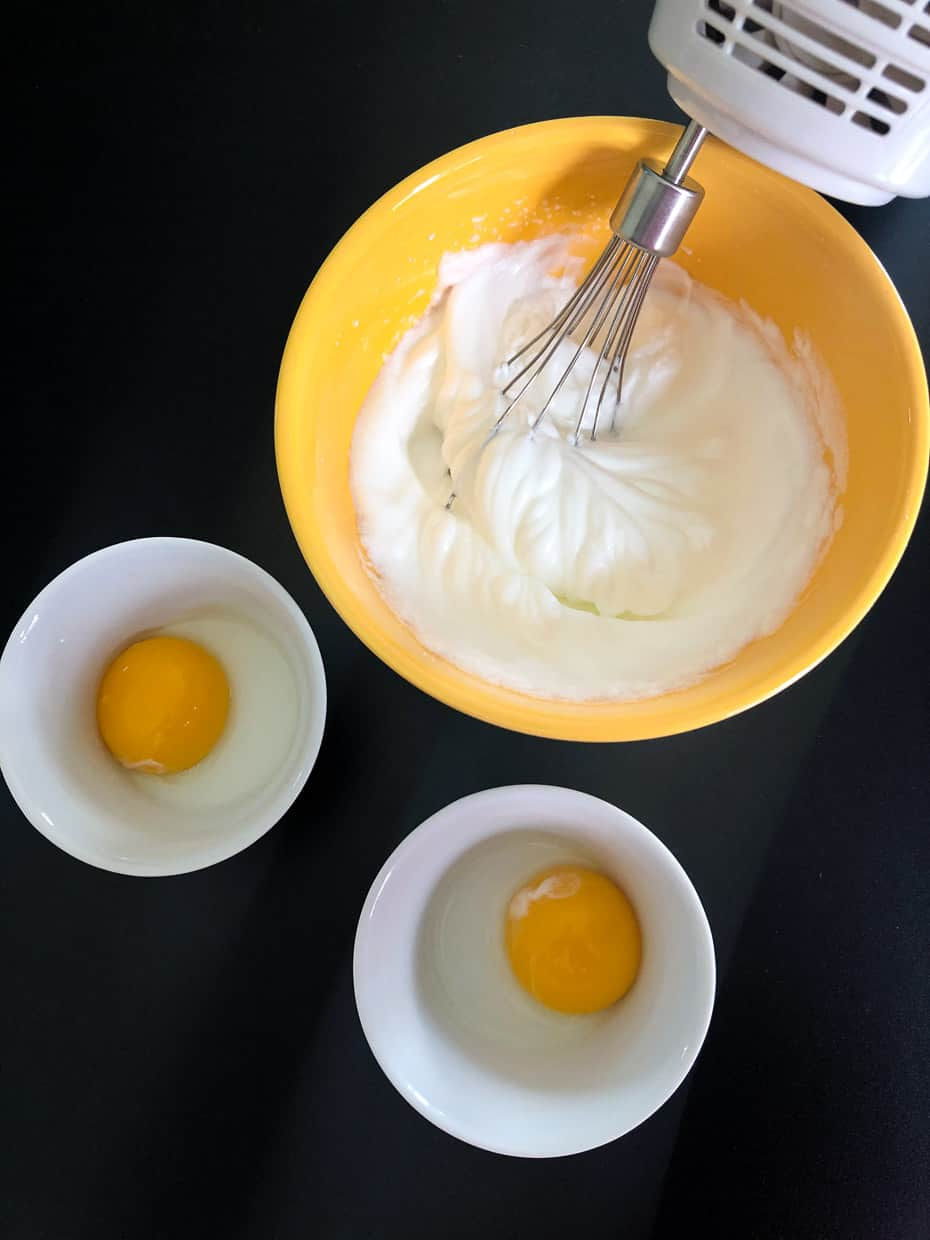 Egg whites being whipped in yellow bowl overhead shot