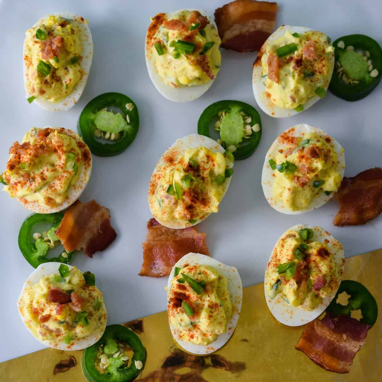 Jalapeno Bacon Deviled Eggs on white and gold platter overhead shot