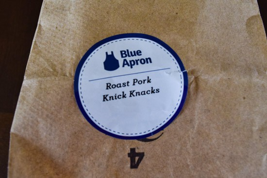 blue apron label on brown bag that says roast pork knick knacks