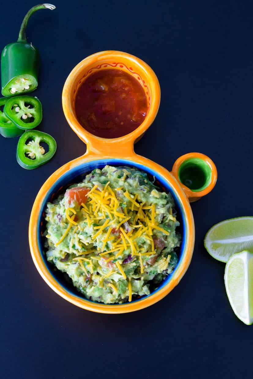 Cheesy Guacamole in Mexican dish with sliced jalapeño