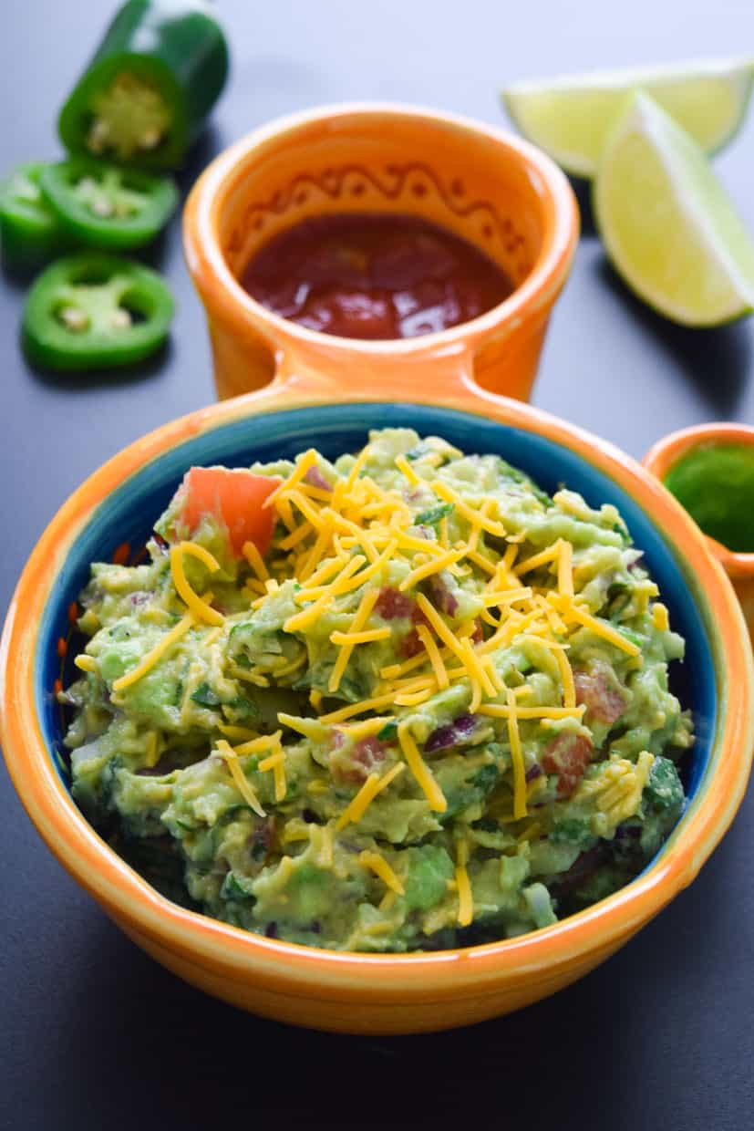 Cheesy Guacamole served in Mexican bowl with lime and jalapeños