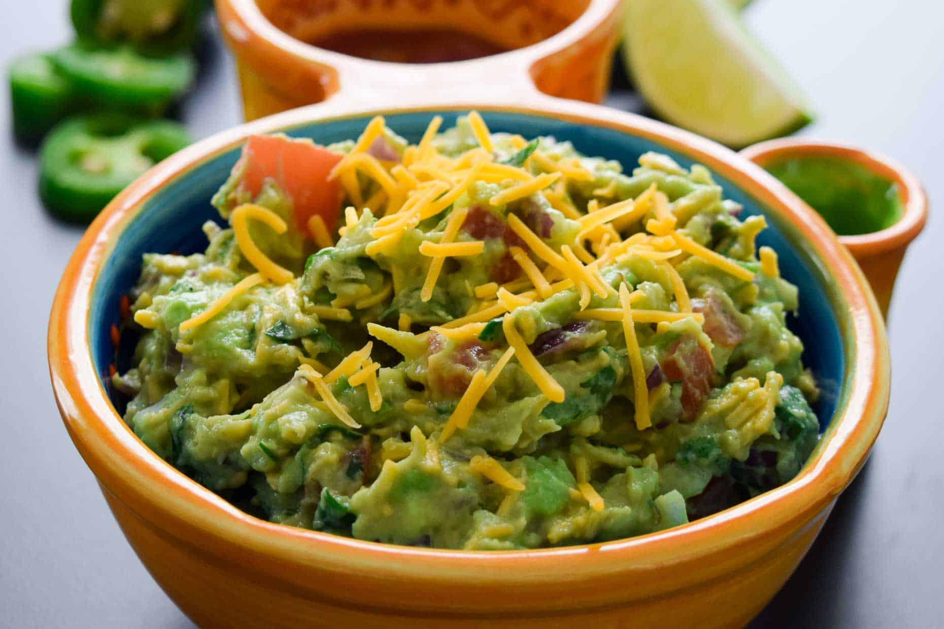 Cheesy Guacamole served in Mexican dish side view