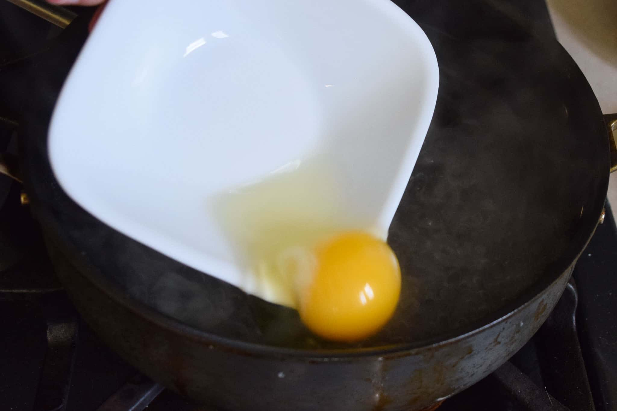 Raw egg being poured from small white bowl into skillet of water