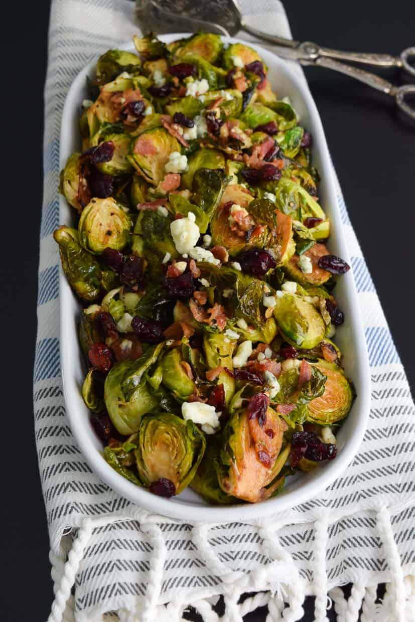 Brussels Sprouts with Bacon and Blue Cheese in platter on striped towel ready to be served