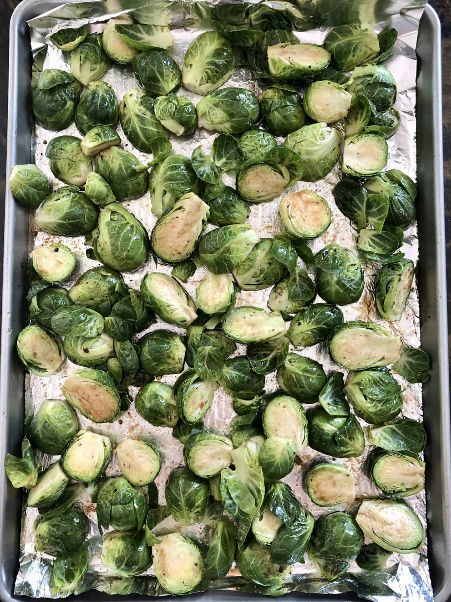 Brussels sprouts on baking sheet ready to be roasted
