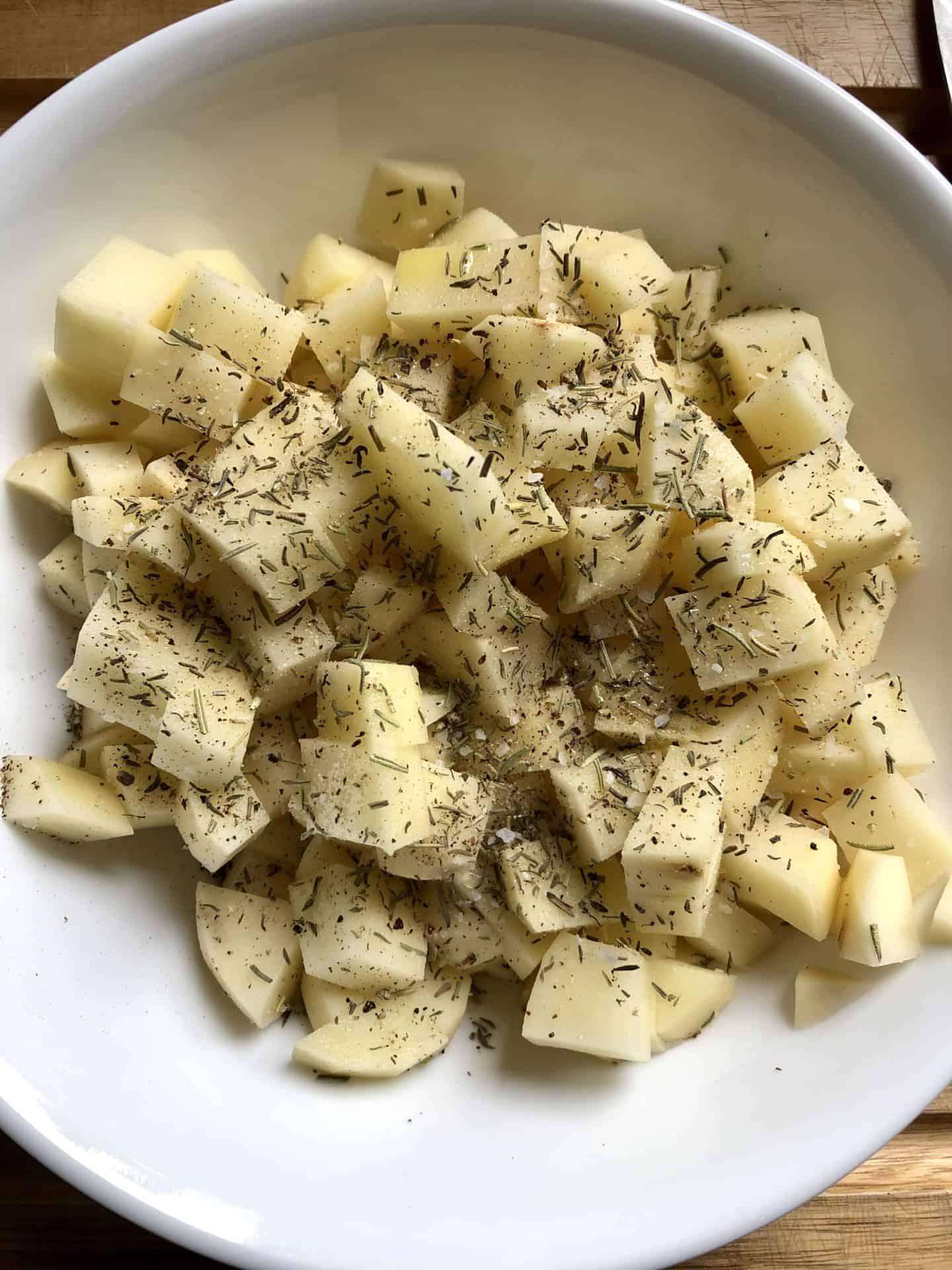 diced potatoes in bowl with seasonings