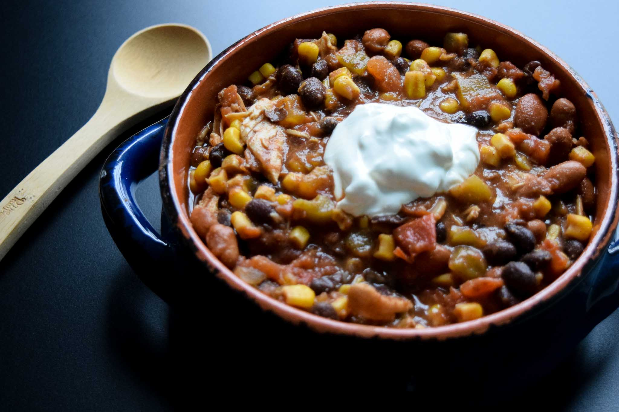 Crockpot Chicken Mexi-Chili in blue and orange bowl topped with sour cream