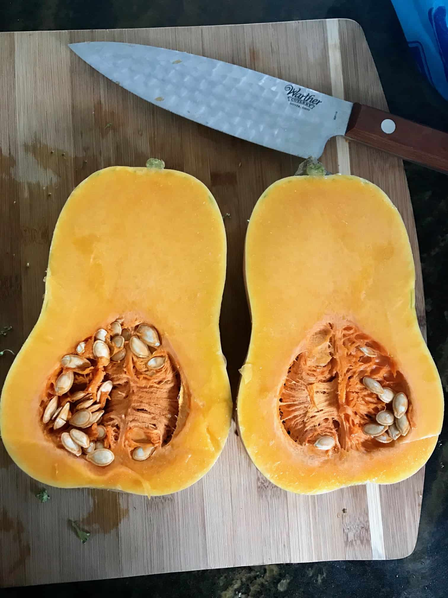 Butternut squash on cutting board cut in half