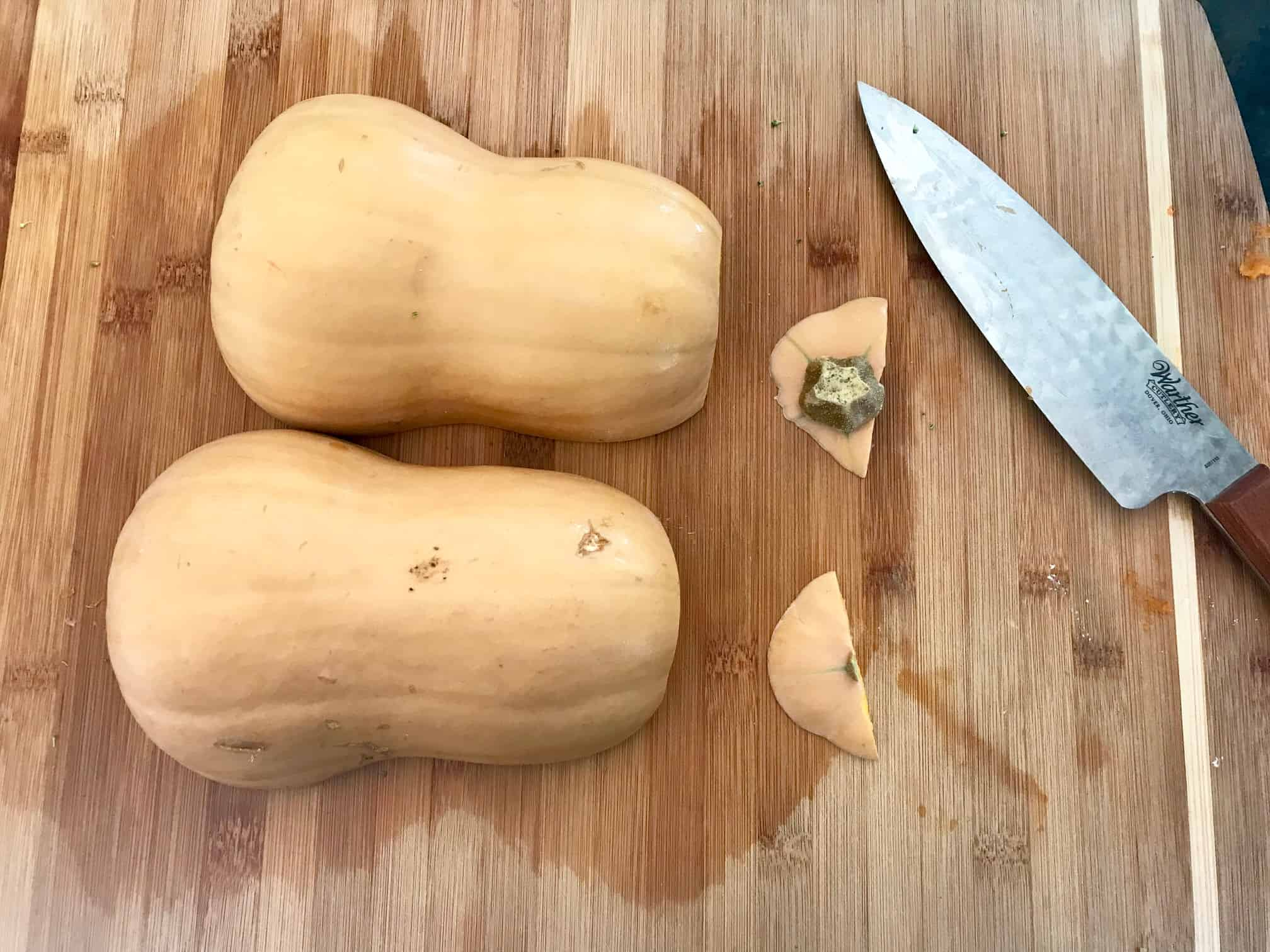 Butternut squash on cutting board cut in half with tops cut off