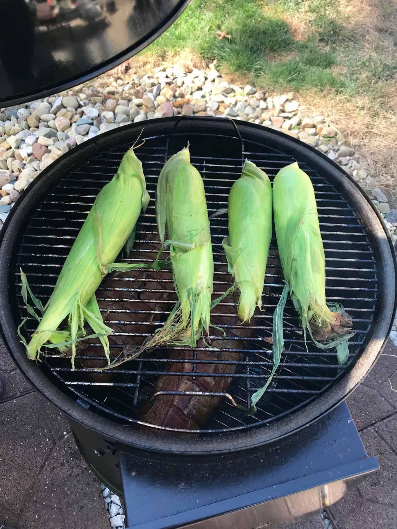 Corn on the cob still in husks on weber grill