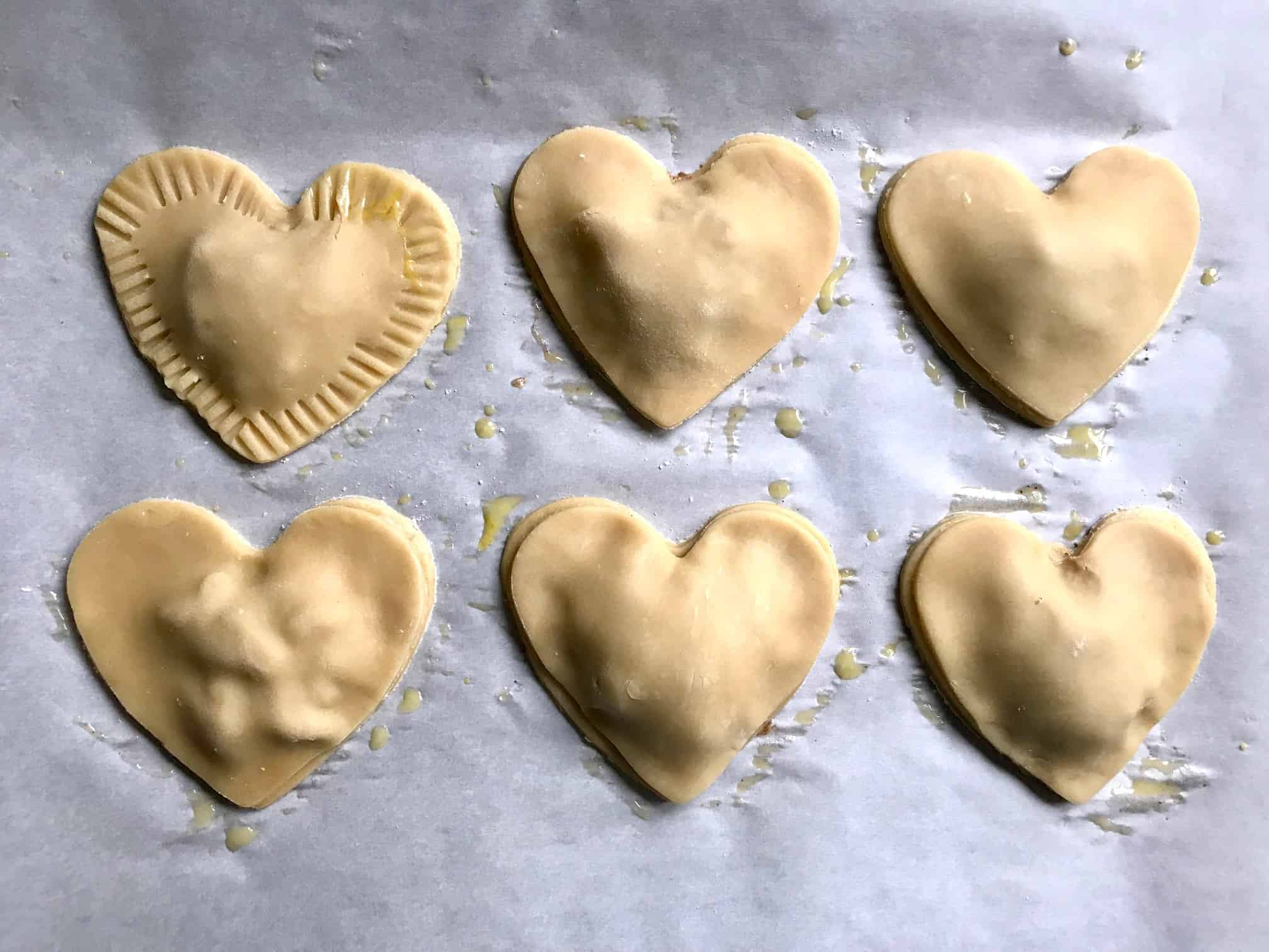 Apple Pie heart shaped pastries on baking sheet pressing edges down with fork overhead shot