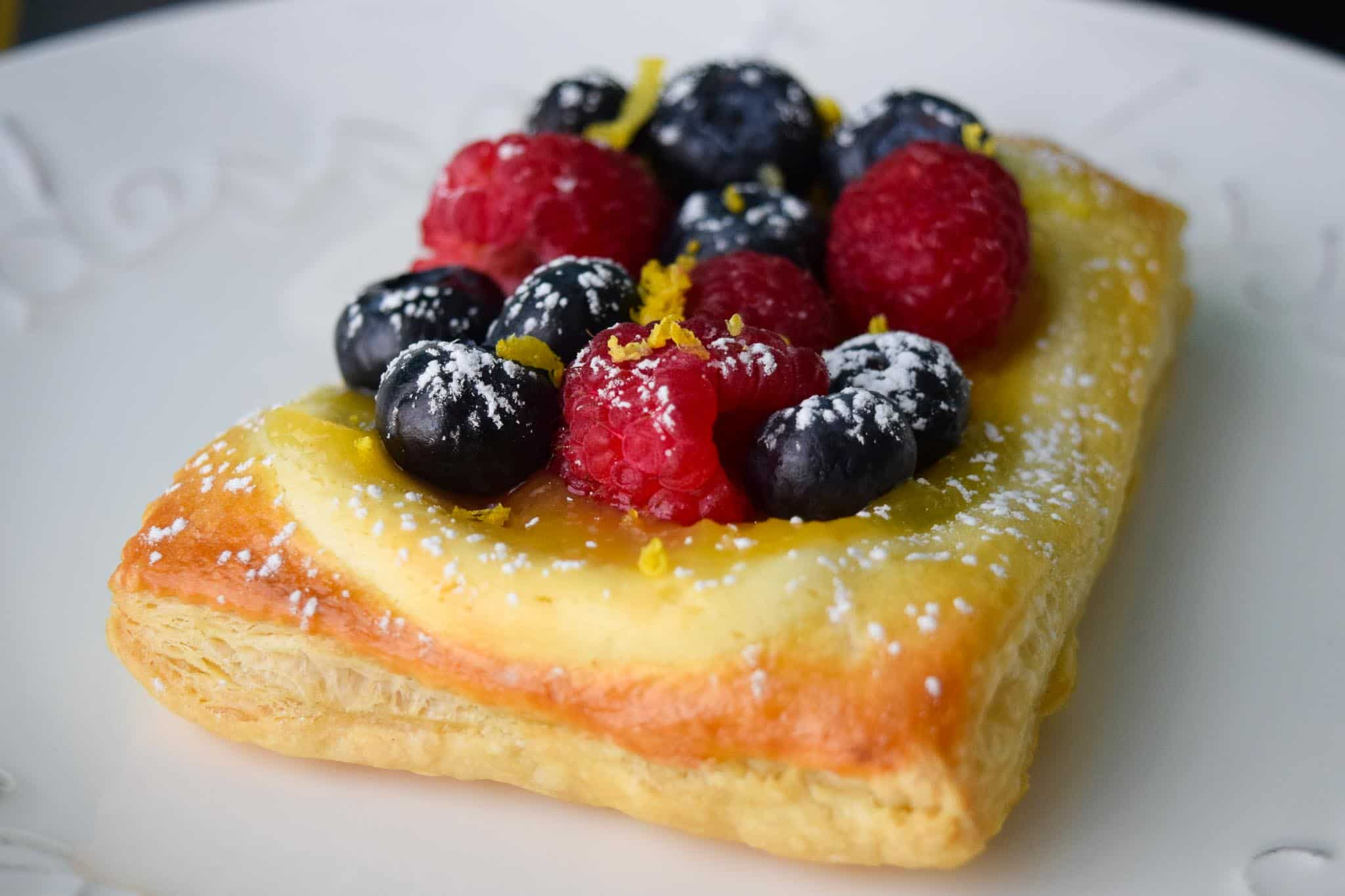 Lemon and Berry Cheesecake Puff on white dessert plate side view