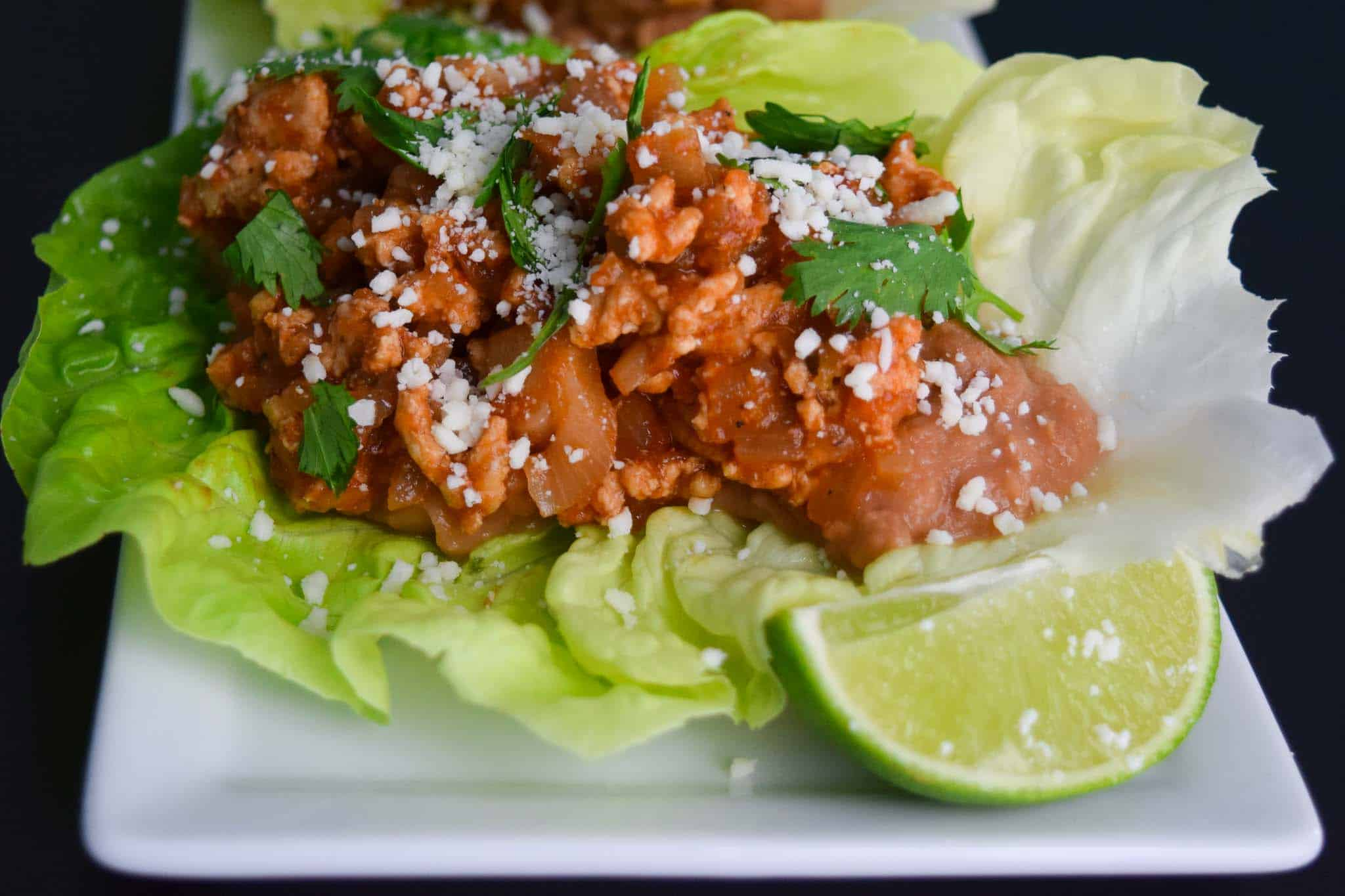 Chicken Taco in Lettuce Wraps on white platter close up view