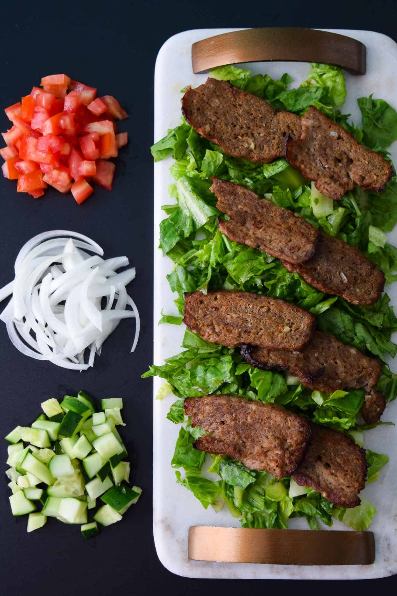Gyro Meat on white platter with toppings beside it overhead shot
