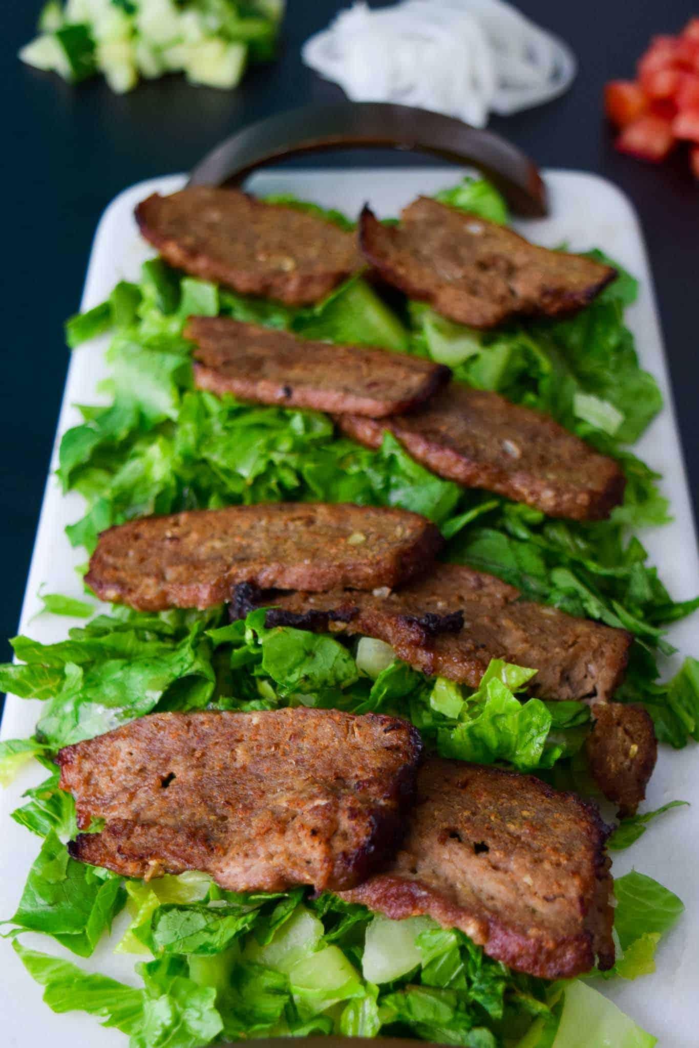 Gyro Meat sliced on bed of lettuce on white platter