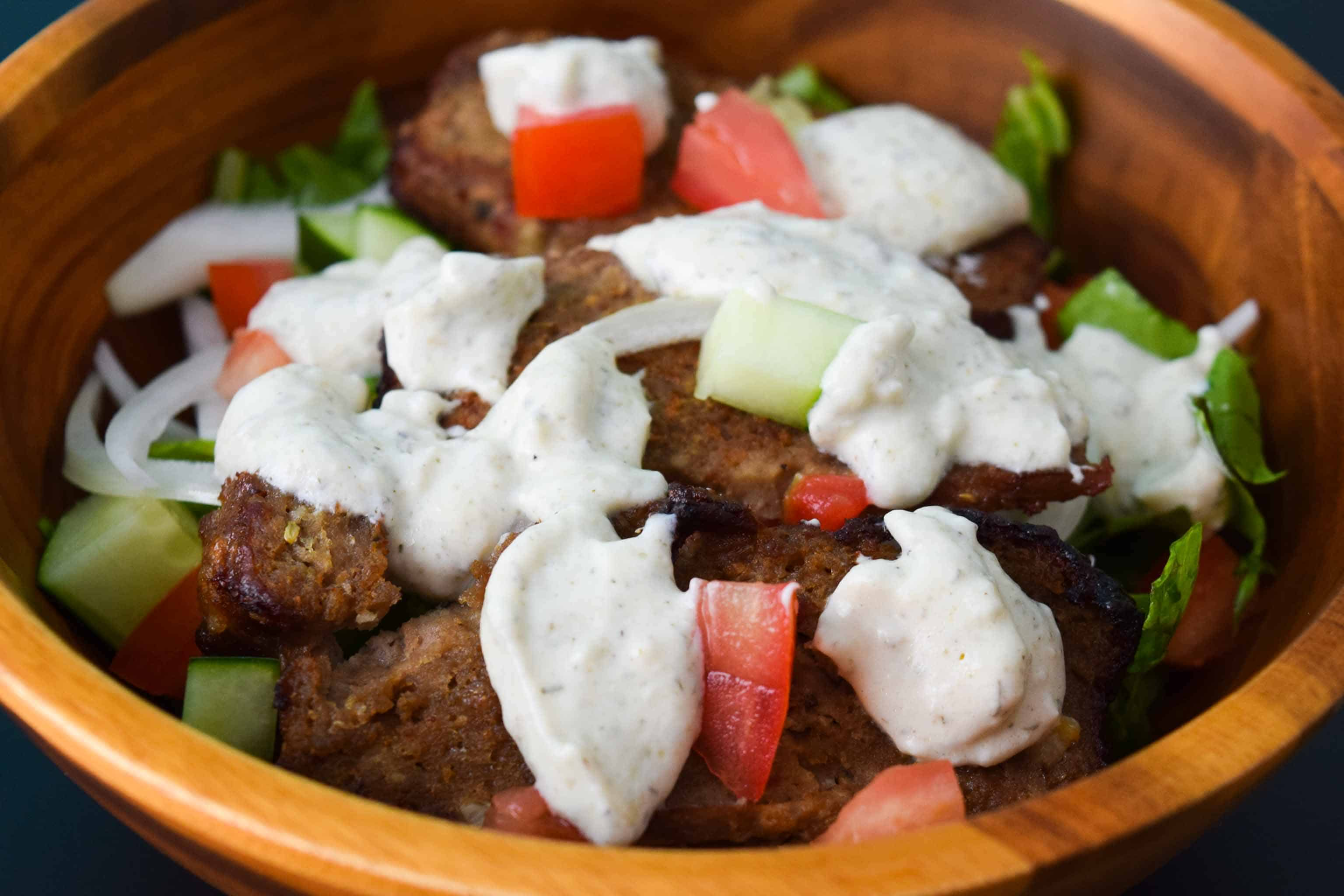 Gyro Meat in salad bowl close up topped with tzatziki