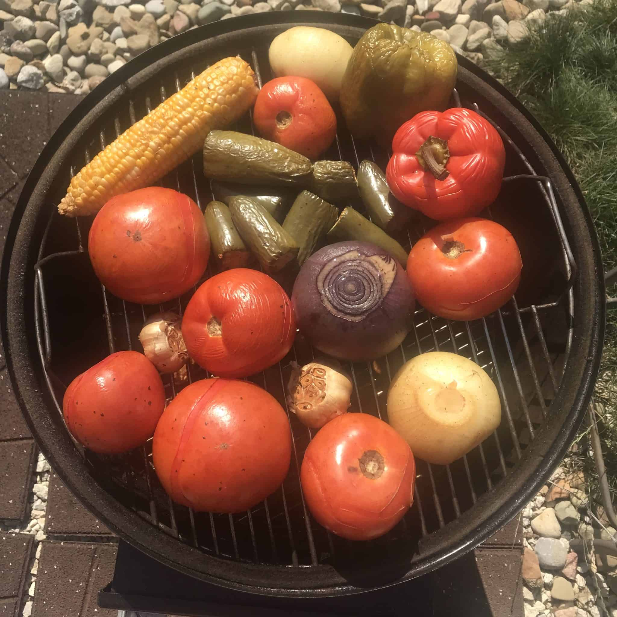Fresh vegetables that have been smoked sitting on weber grill over head shot