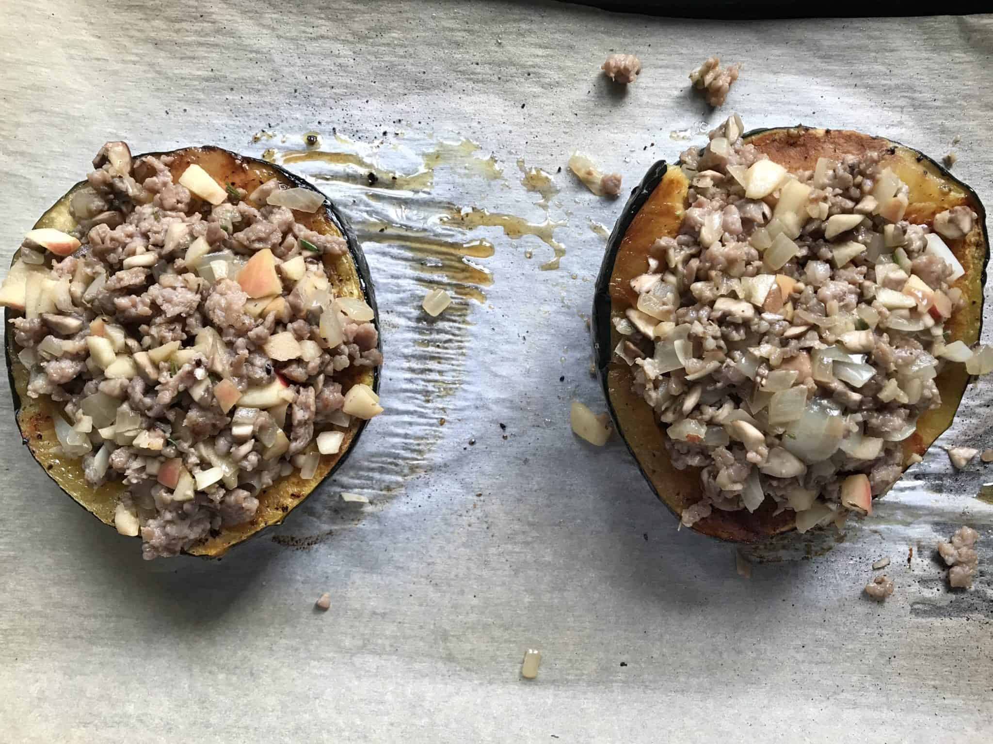 Acorn Squash stuffed with sausage and apple mixture on baking sheet