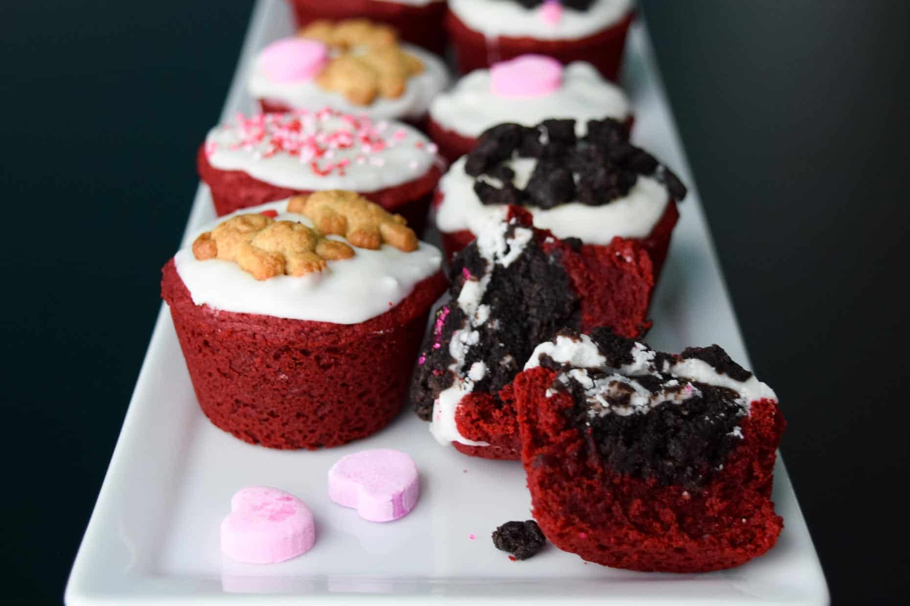Red Velvet Oreo Valentine Cups on white platter with conversation hearts close up view