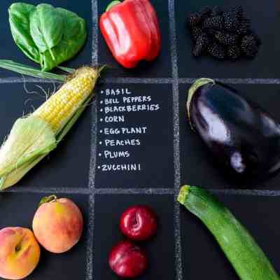 July Seasonal Produce Guide with produce in quadrants on chalkboard