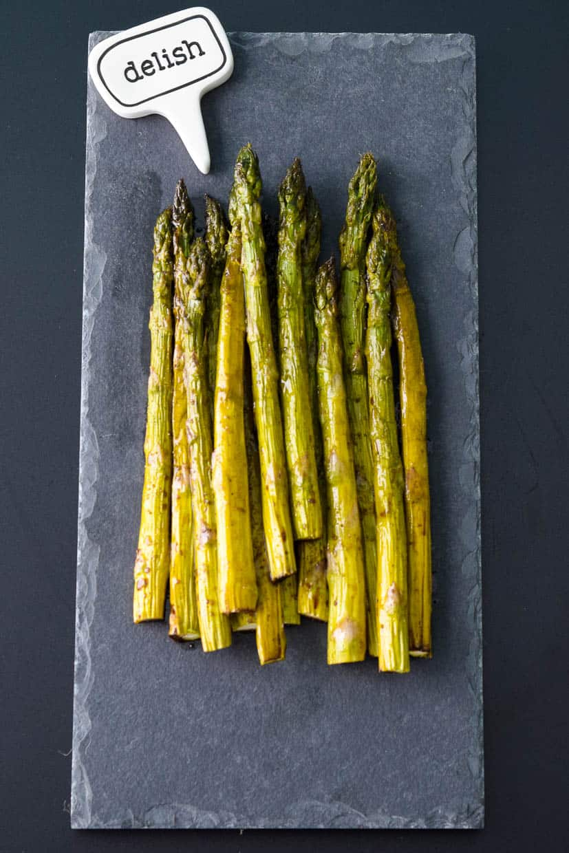 Easy Roasted Asparagus on slate platter with delish sign above it