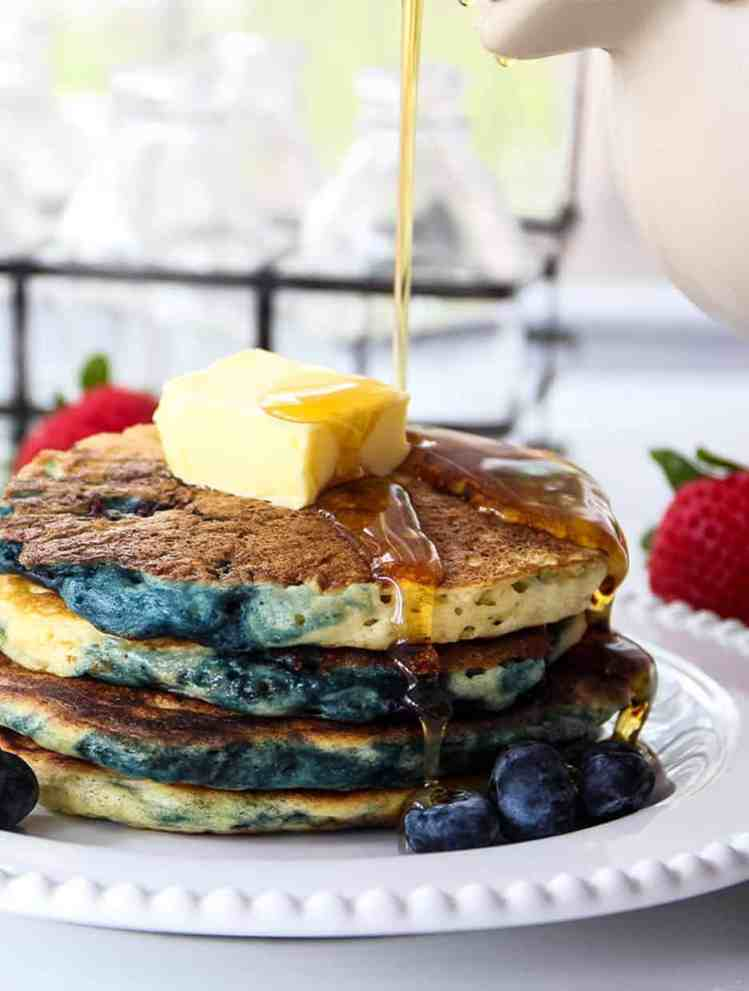 stack of blueberry pancakes with syrup being poured on top