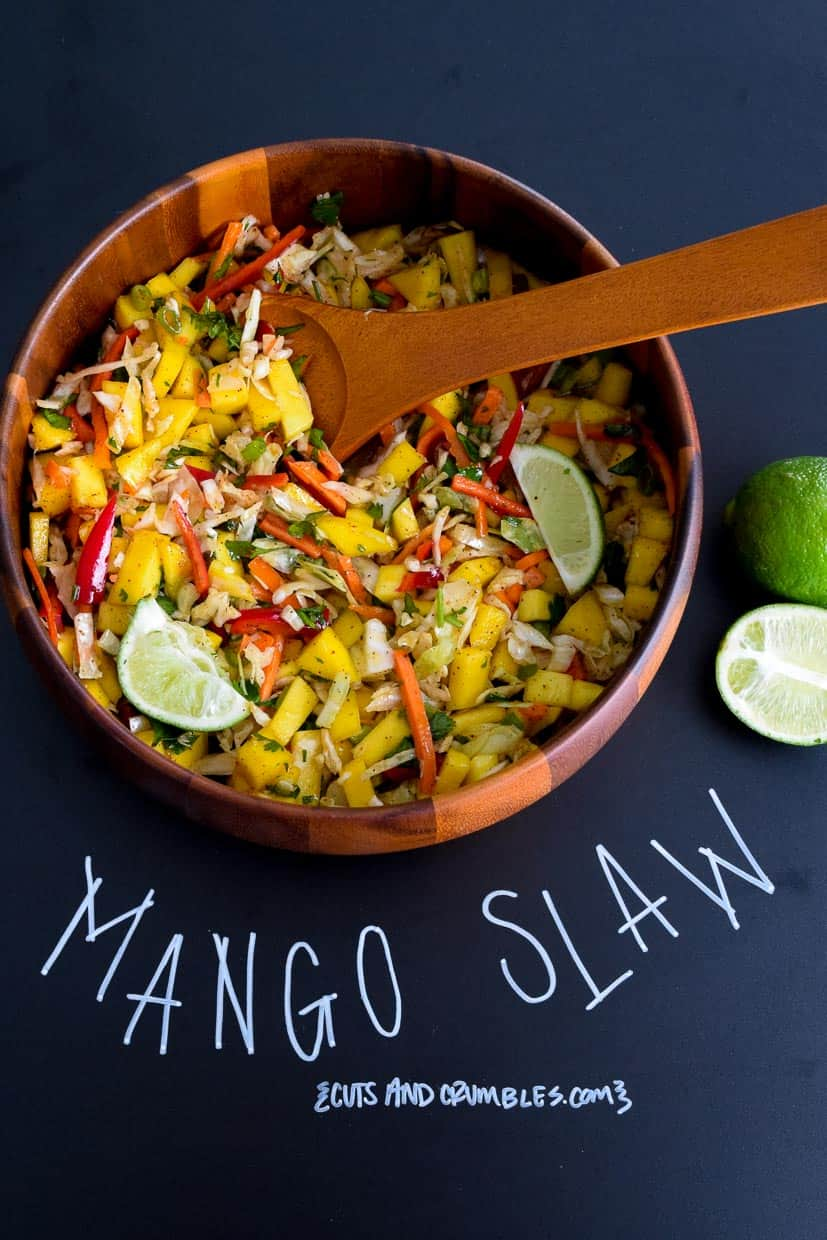 Mango slaw in wooden bowl with title written on chalkboard