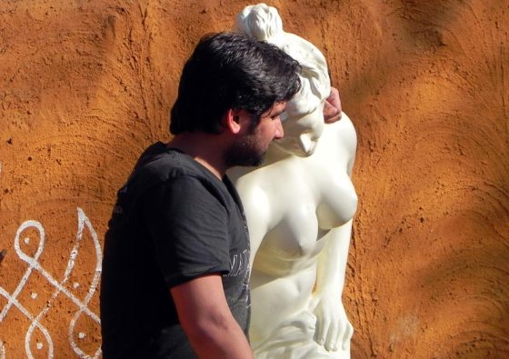 Man posing with a topless statue at Surajkund Fair 2011
