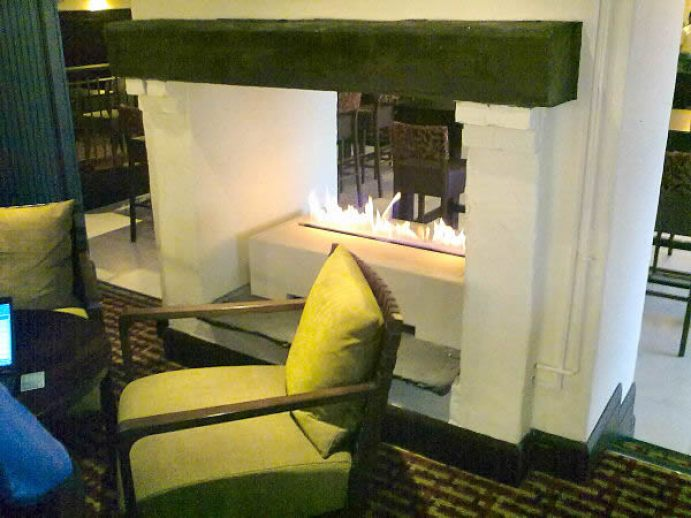 double sided gas fireplace with contemporary box shape and limestone material