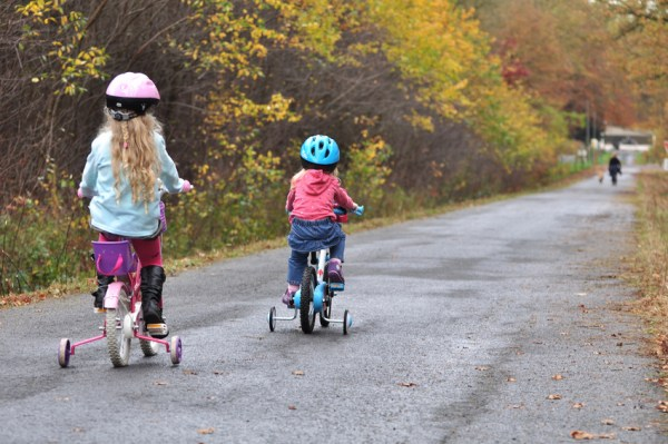 Girls riding on stabiliser bikes
