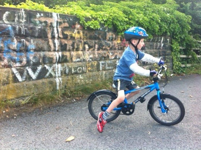 Little boy riding an Islabike Cnoc 16 review for the first time on a family bike ride after learning to ride his bike