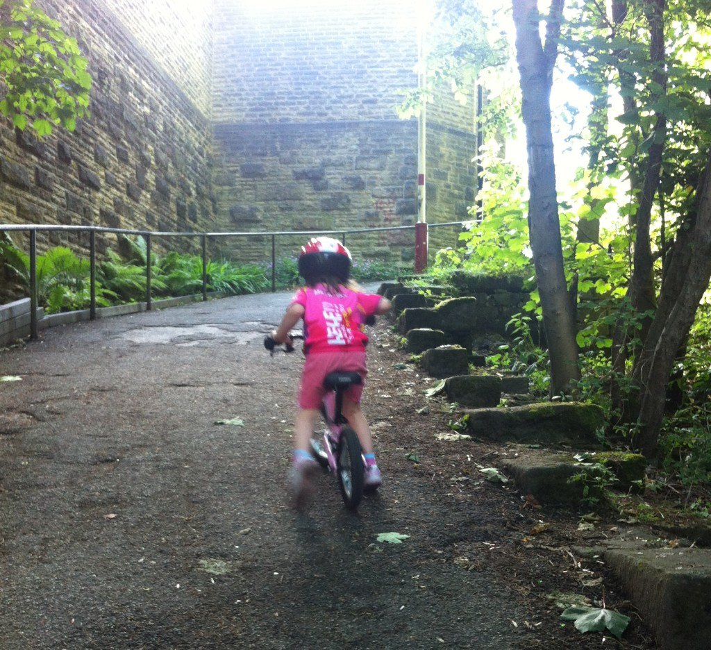 Photo of girl on balance bike riding up steep hill